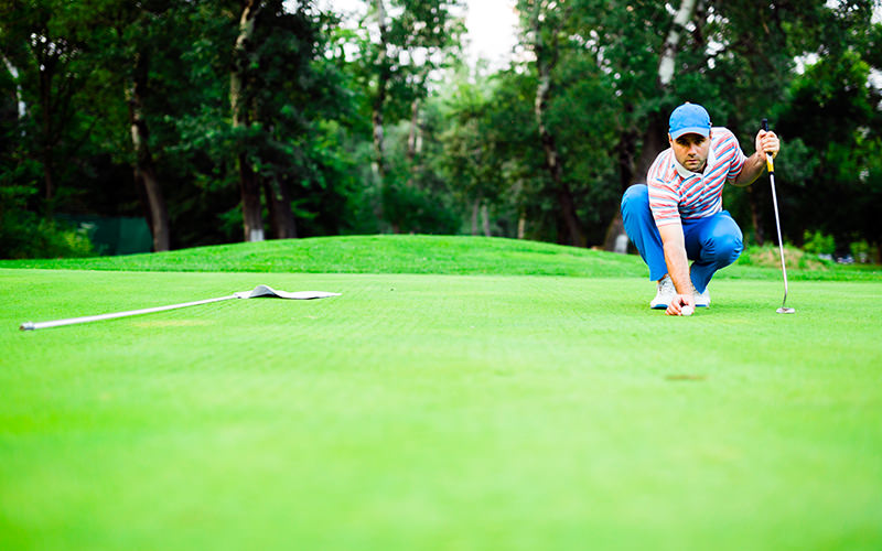A man crouching down on a golfing green and watching the ball