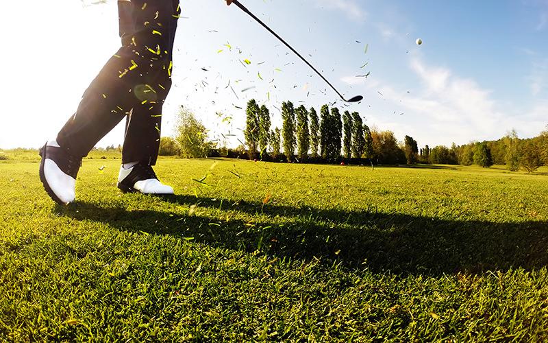 Close up of a man hitting a golf ball