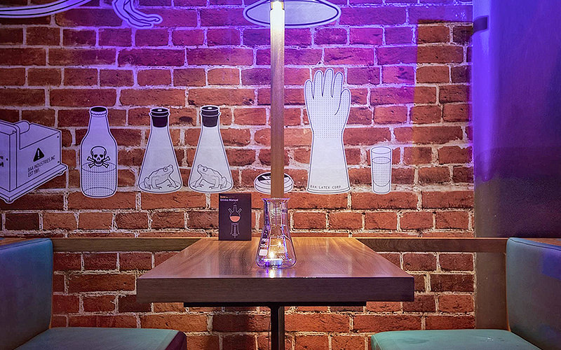A table with a science beaker on top, to a backdrop of an exposed brick wall with scientific drawings on