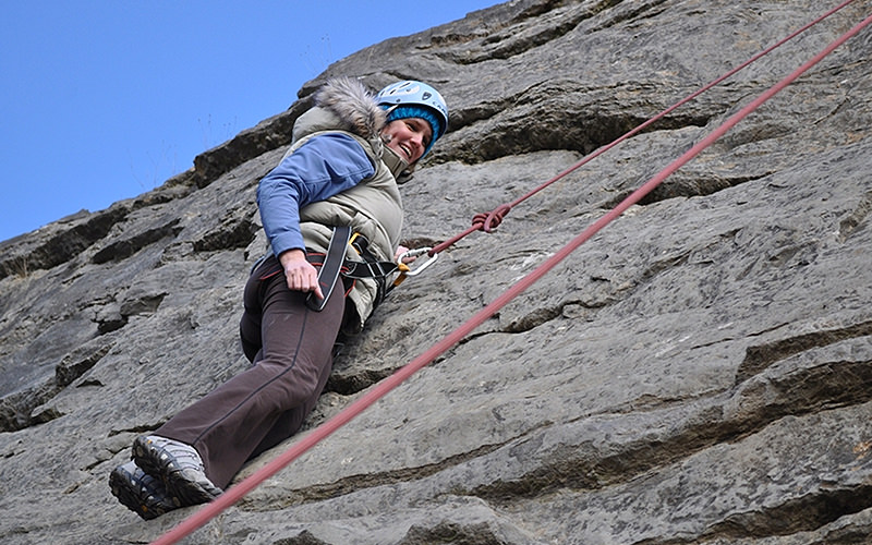 An image of a women taken from below, climbing a wall outdoors with red abseiling ropes