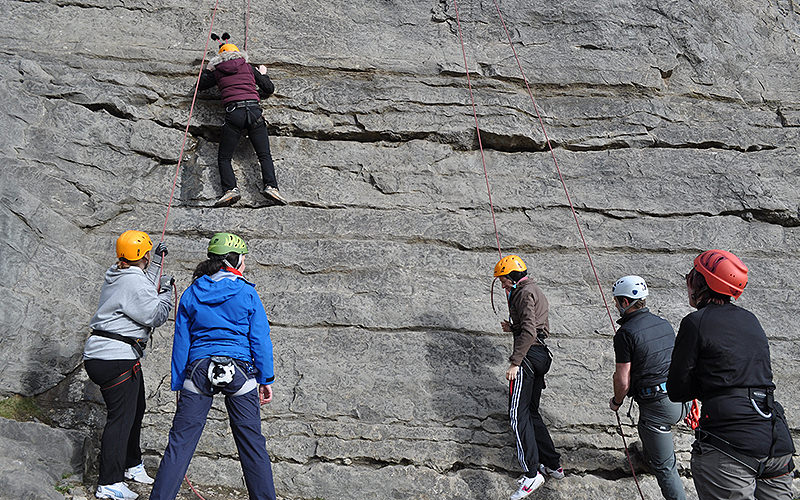 Five climbers at the bottom of a sheer wall, watching a woman climb the wall with climbing ropes attached to her