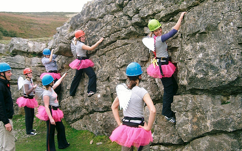 A group of six women wearing pink tutus and angel wings, climbing a sheer wall with an instructor guiding them