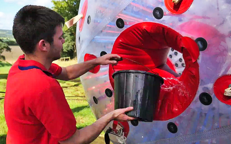 A man in a red shirt pouring water from a bucket into a zorb