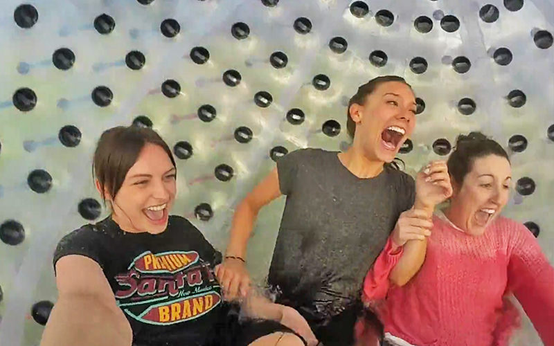 Three women laughing and smiling in a zorb with water