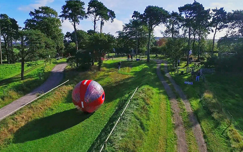 A red zorb rolling down a field