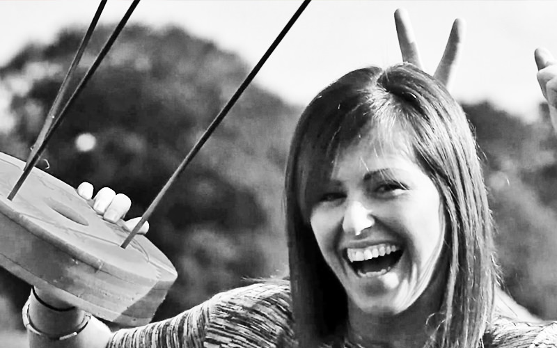 A woman holding an archery target with three bows in it