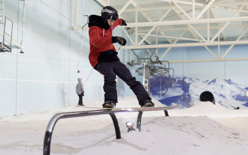 A man snowboarding on a rail in an indoor snow park