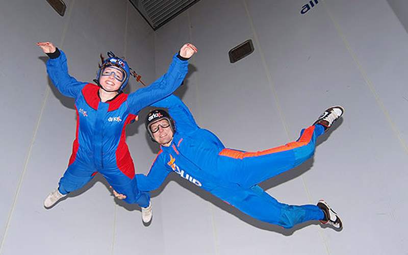 Two people floating in the air in a skydiving simulator