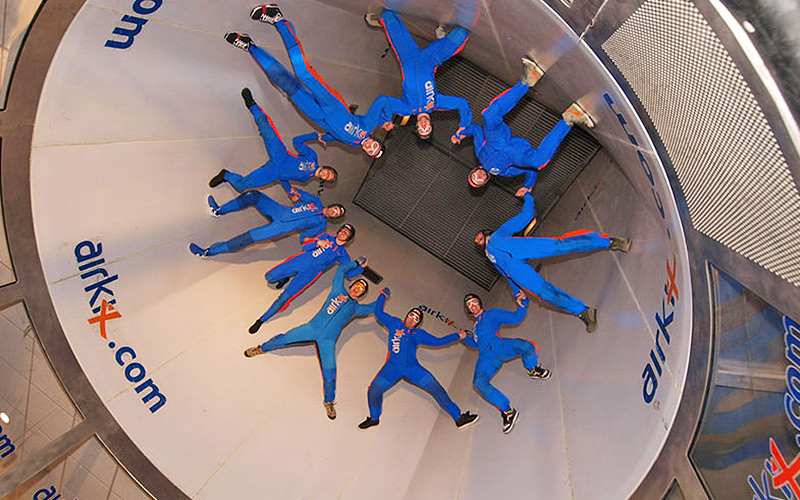 A group of people in blue jumpsuits floating in the air in a skydiving simulator