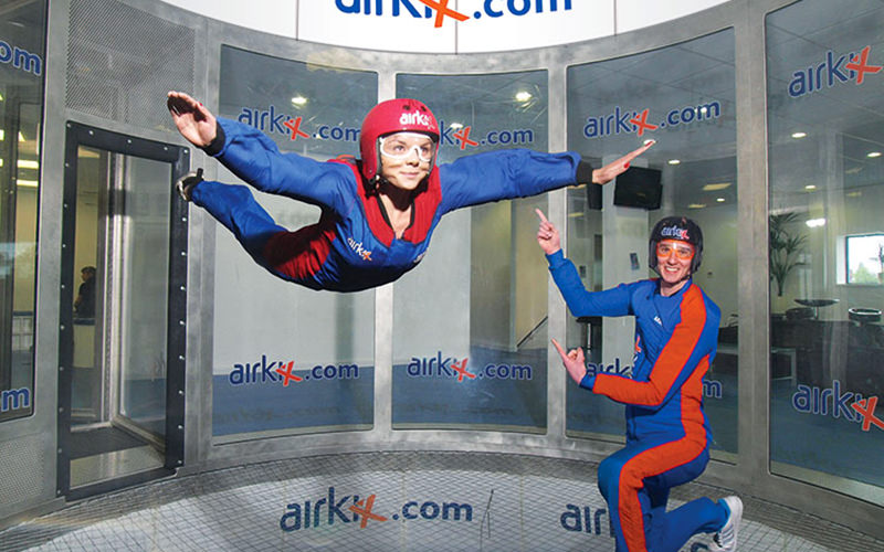 A woman floating in the air in a skydiving simulator, with a man on his knees and pointing at her