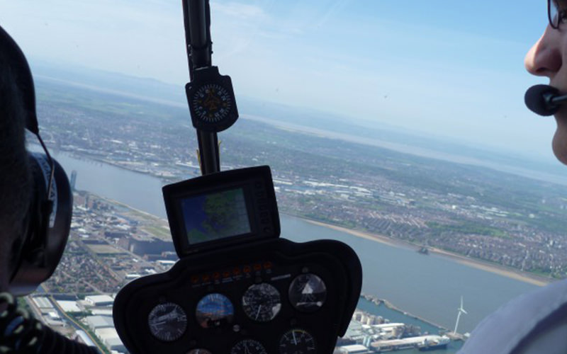 A shot from the cockput of the helicopter, looking down over a city