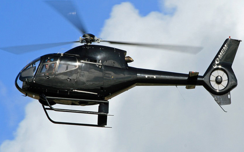 A black helicopter flying in the air