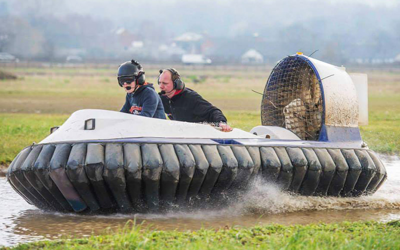 Two men in a hovercraft, driving on top of water