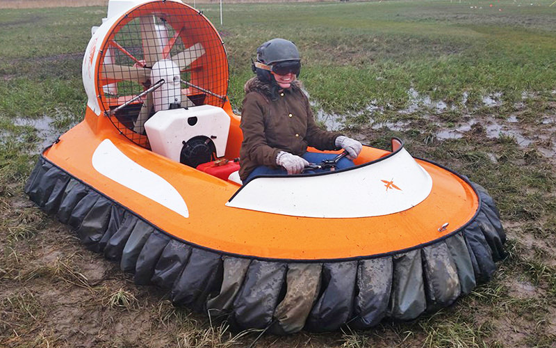 A woman sat in an orange hovercraft in a muddy field