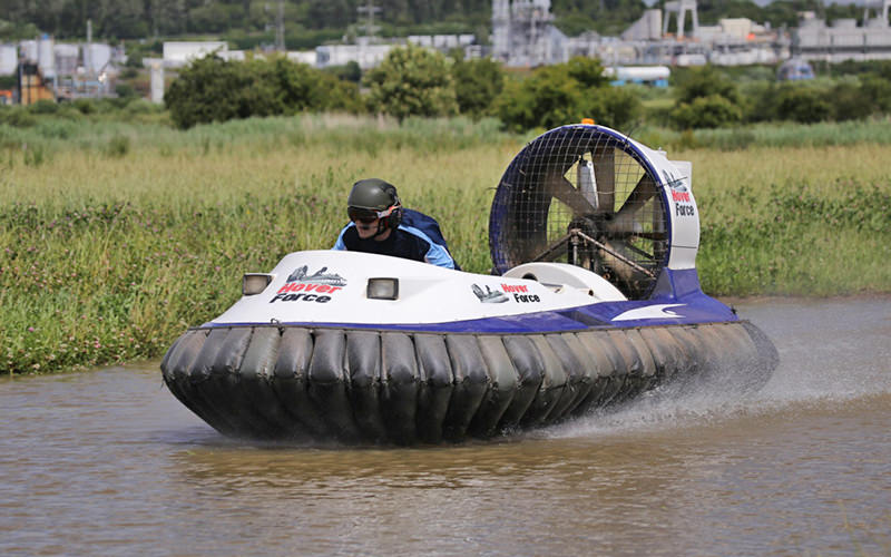 A man driving a hovercraft over water