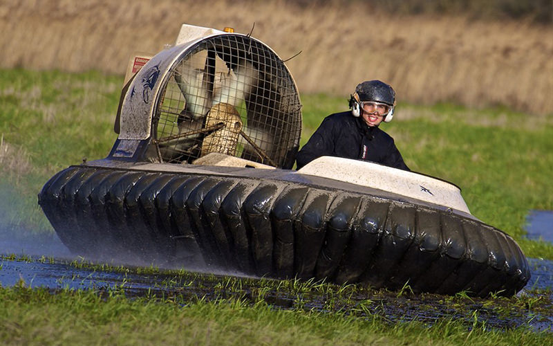 A man in a hovercraft, driving over a muddy field