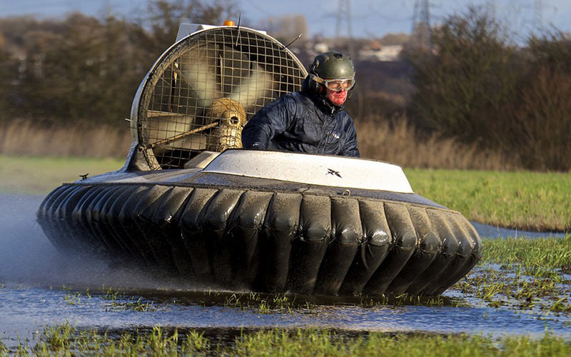 A man driving a hovercraft over a wet field