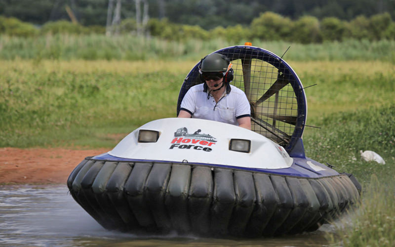 A man in a white T-Shirt, driving a hovercraft in a field