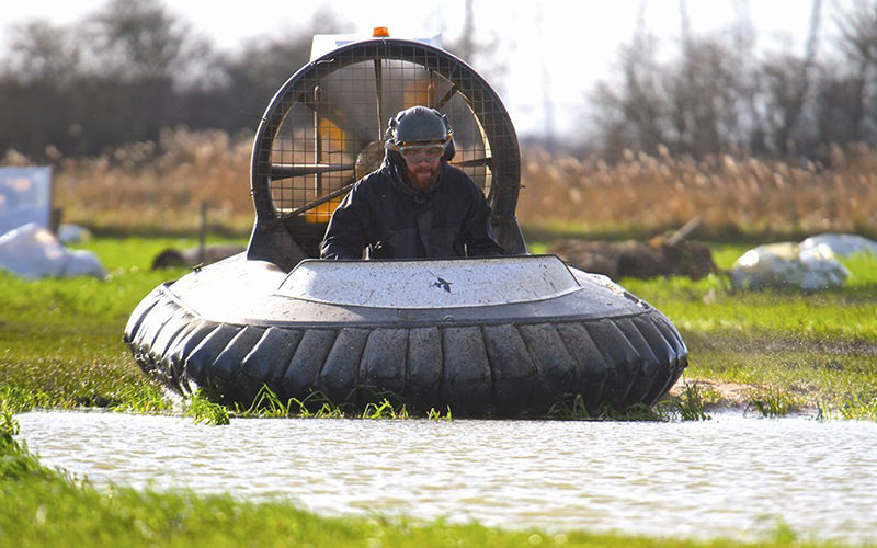 A man about to drive a hovercraft over water in a field