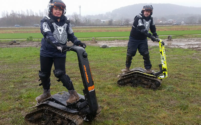 Two people stood on DTV Shredders in a muddy field