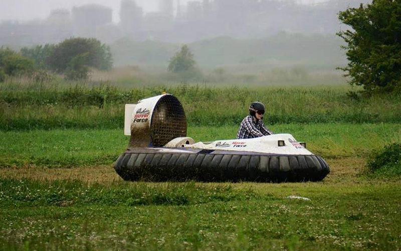 A person driving a racing hover across the grass