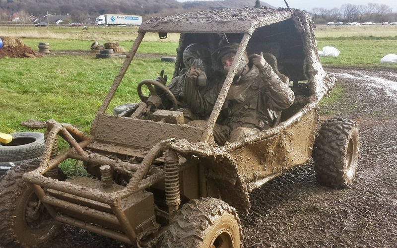 Two men in an extremely muddy mud buggy, with their hands in the air
