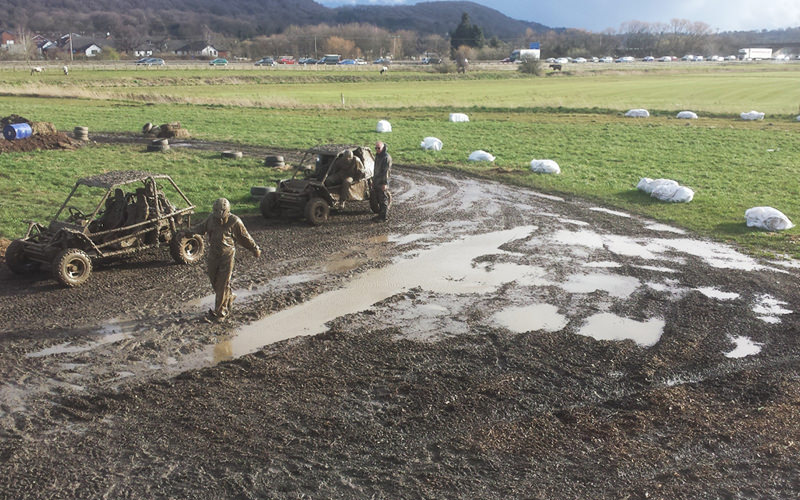 A person walking through the mud with two mud buggies in the background