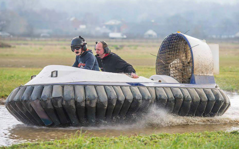 Two people riding a racing hover over the water