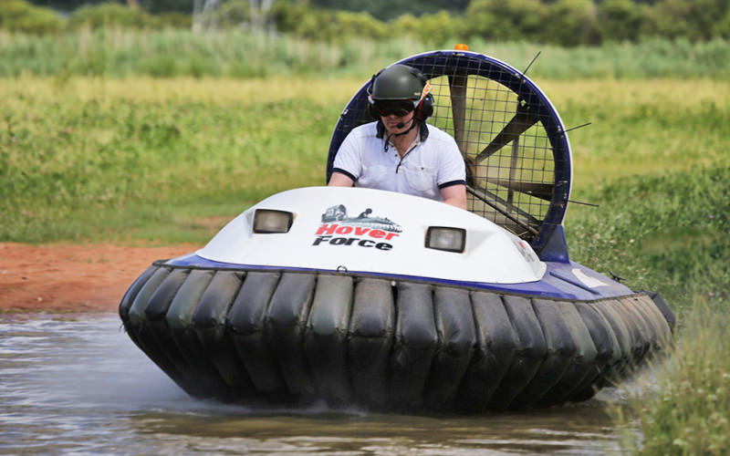 A man driving a hovercraft with a helmet and hard hat on