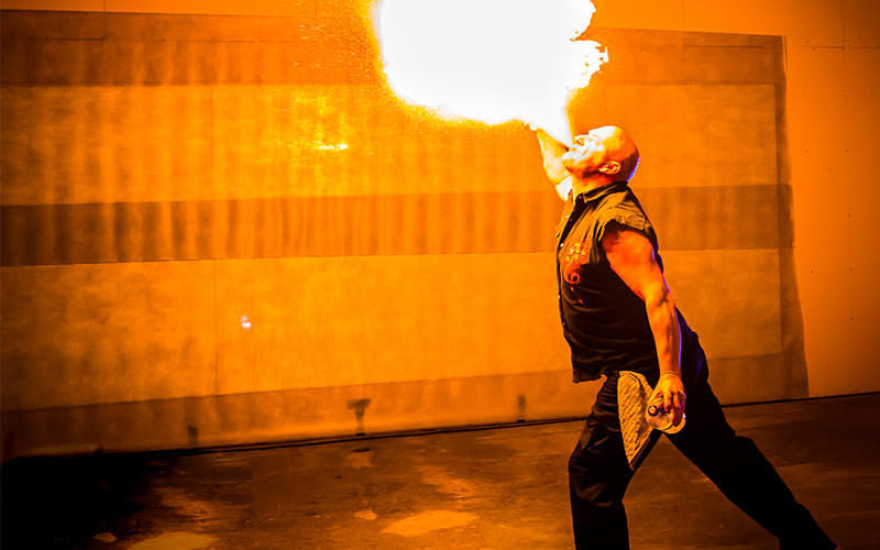 A man firebreathing, to a backdrop of a wall illuminated orange
