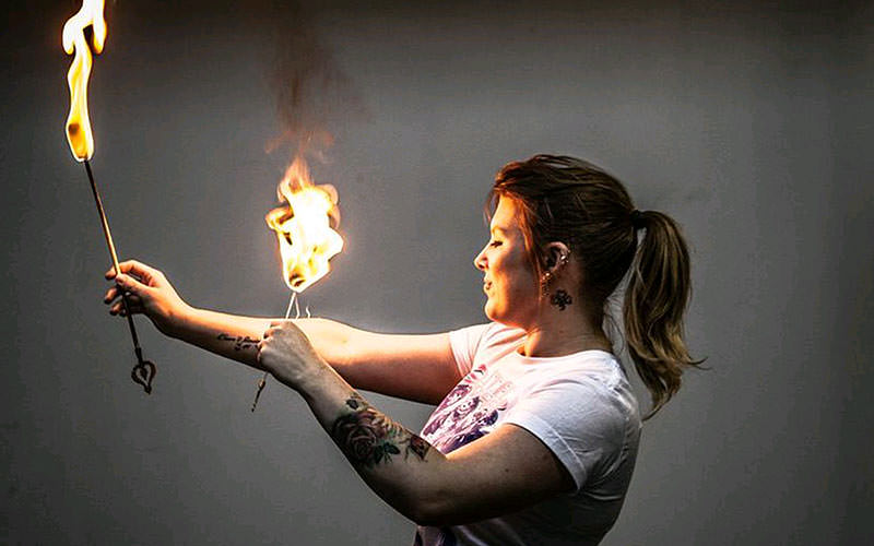 A woman holding flaming sticks to her skin and rolling over her arms