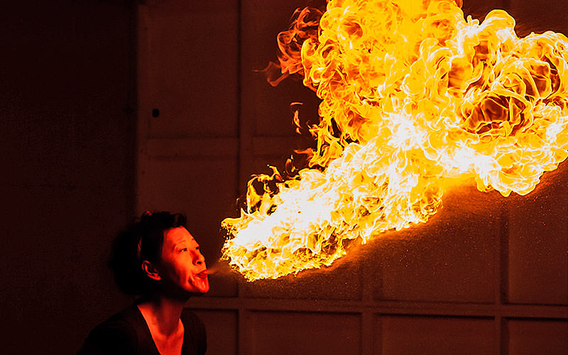 A woman blowing a huge flame out of her mouth