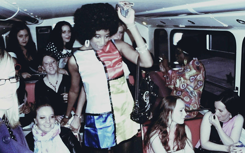 Some people on the party bus, dressed in 60s and 70s style clothing