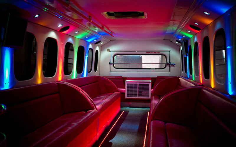 The interiors of a party bus with red seating and disco lighting