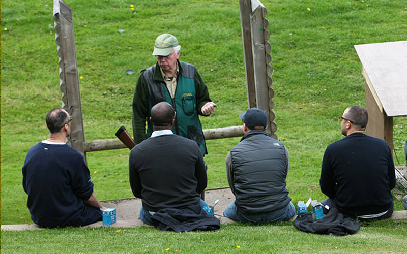 Four men receiving safety instruction from a clay pigeon shooting instructor