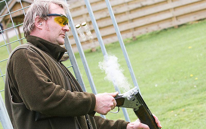 Man wearing goggles and ear plugs, reloading his gun