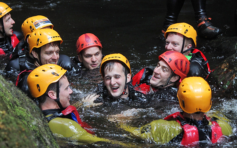 Nine men in the water together during canyoning, with yellow and red hard hats on
