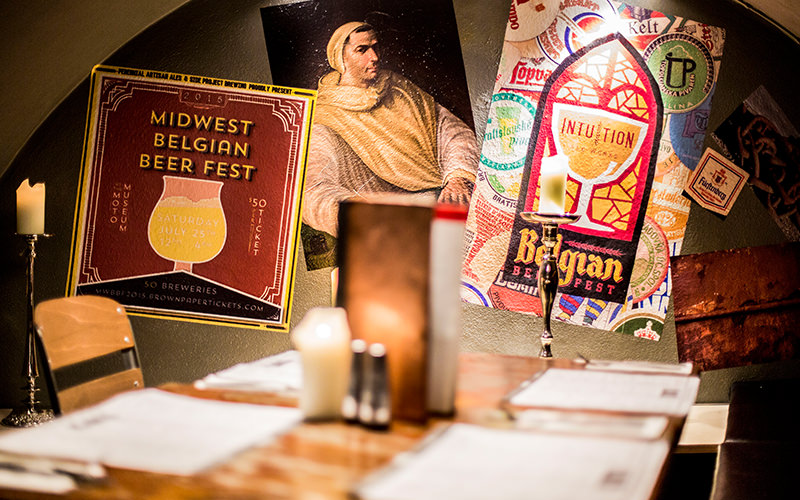 A close up of posters on the wall, with a table in the foreground, at Belgo Centraal, London
