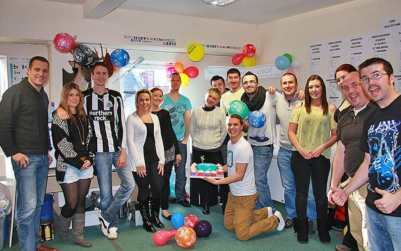 A group of men and women posing with balloons, with one man on his knees on the floor holding a cake