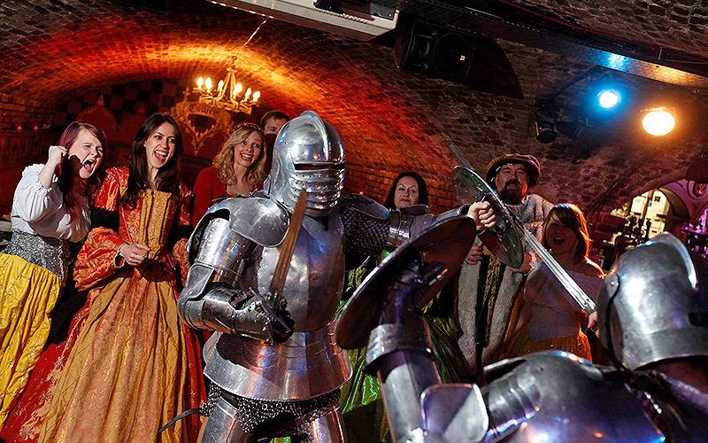 People dressed in Medieval outfits watching two armoured knights fighting