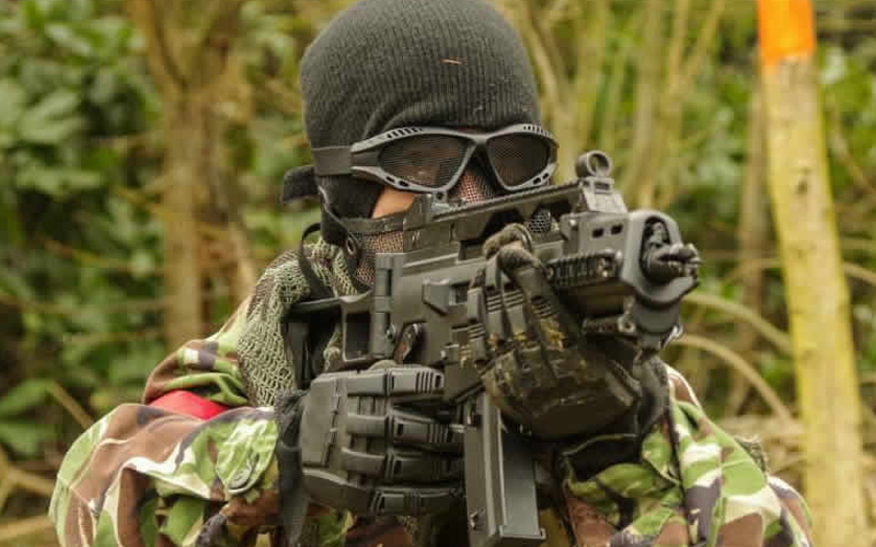 Girl playing airsoft in full army gear