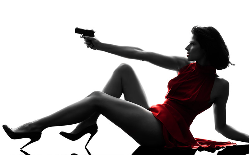 Sexy deadly woman in a red dress holding a gun