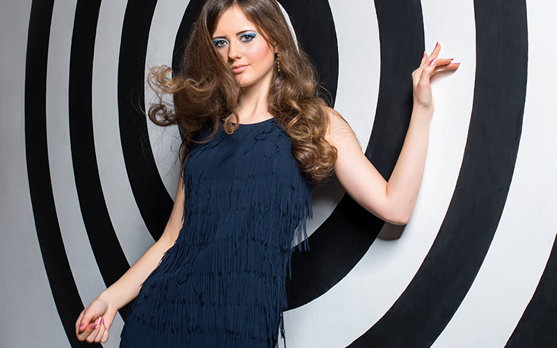 Retro chic in a blue tassle dress with blue eye makeup against a black and white target wall