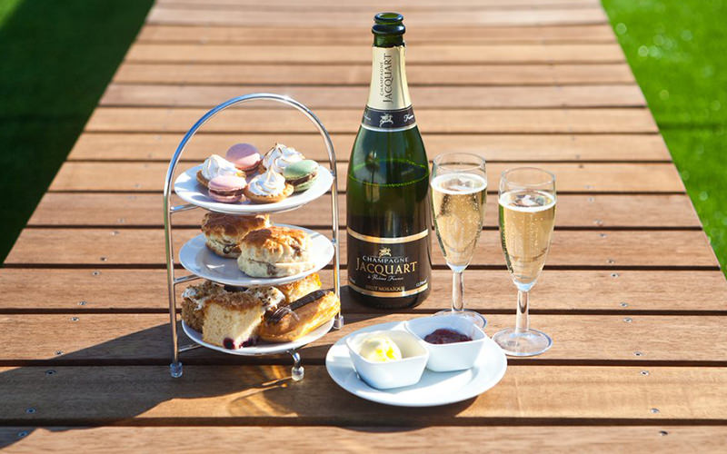Afternoon tea with champagne on a wooden walkway