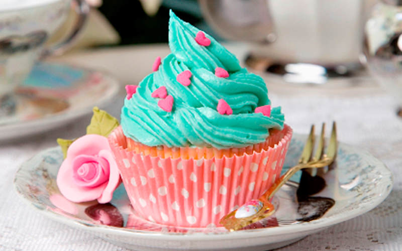 Cupcake in red and white case, decorated with green icing and pink hearts