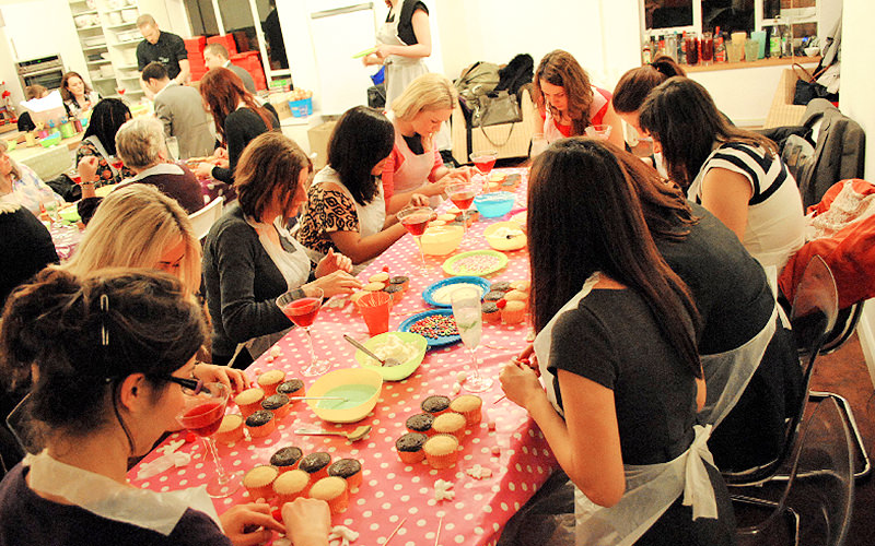 Group of ladies gathered around a table decorating their cupcakes.