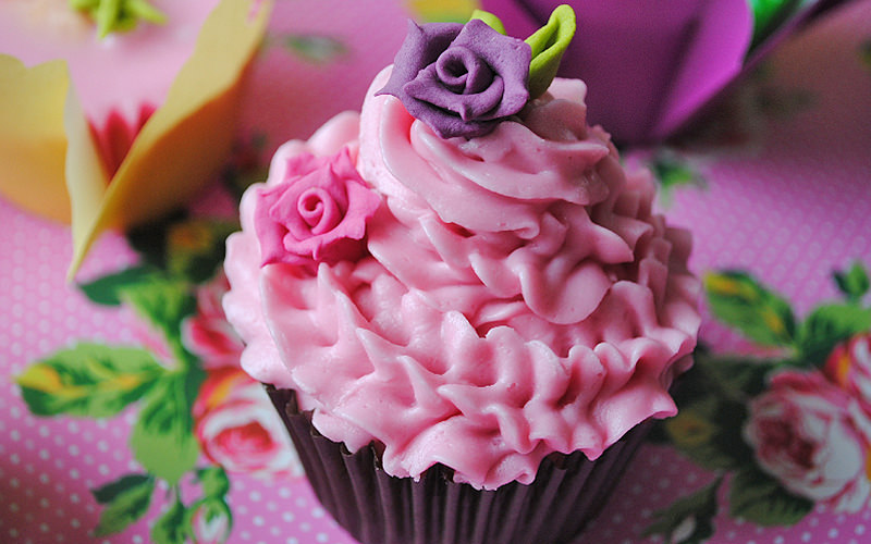 Cupcake decorated in pink icing, with pruple and pink flowers and sat on flower patterned table top