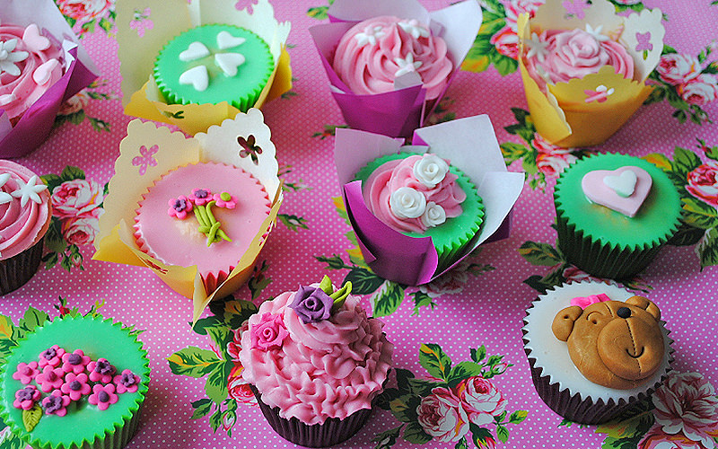 A selection of pink and green cupcakes on a pink flower table top