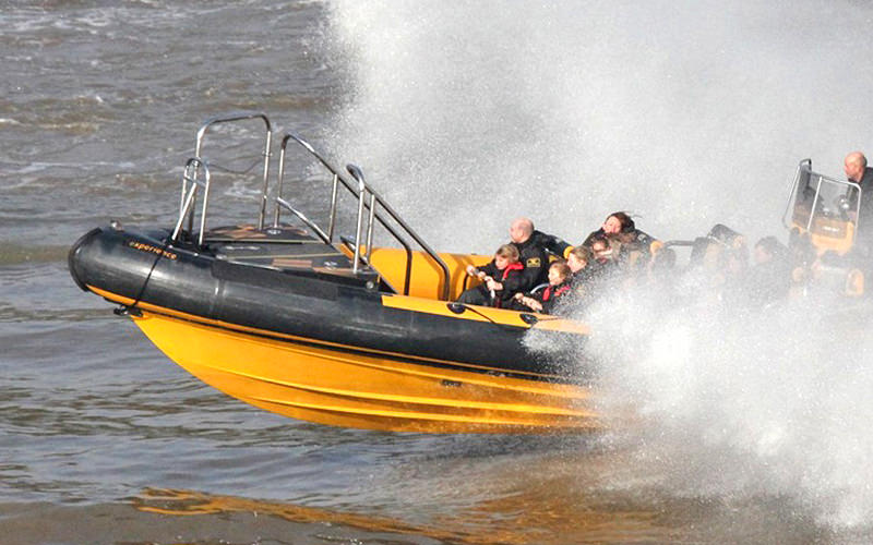 A yellow RIB boat speeding creating lots of white splash
