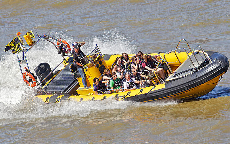 Yellow RIB boat riding along The Thames